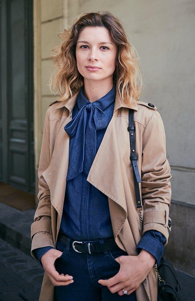 Comptoir des cotonniers Pauline porte le trench long fluide, la chemise denim avec lavallière et un jean slim.